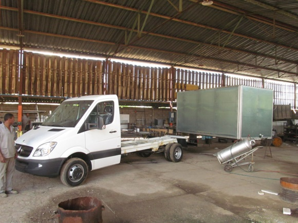 Sprinter e estrutura do baú atrás com cilindro de gás à frente e mecânico observando o caminhão Blog Vem Por Aqui