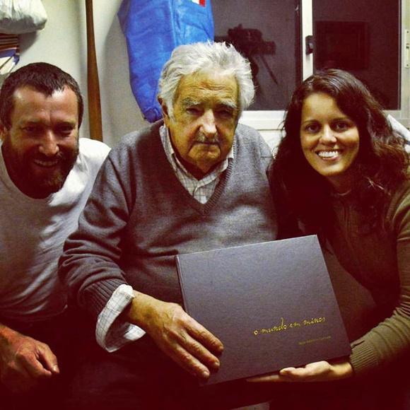 Renato e Glória com o ex-presidente do Uruguai Pepe Mujica, no meio, segurando o livro do casal Blog Vem Por Aqui