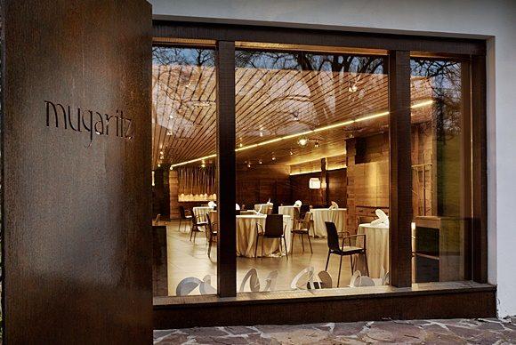 Entrada do restaurante com nome escrito na parede de madeira e parede de vidro onde é possível ver as mesas do salão Blog Vem Por Aqui