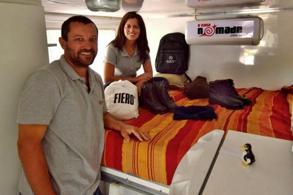 Glória sentada na cama com Renato em pé, ao lado e botas e roupas em cima Blog Vem Por Aqui