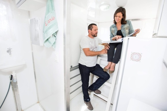 Glória sentada na cama, Renato nos degraus da escada e, do lado esquerdo, a pia do banheiro, do lado direito, a geladeira Blog Vem Por Aqui