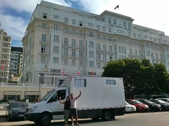 Motorhome parado em frente ao Copacabana Palace e Renato e Glória na frente, de braços levantados Blog Vem Por Aqui
