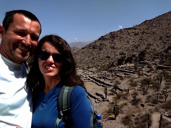 Renato e Glória sorrindo com paisagem desértica ao fundo Blog Vem Por Aqui