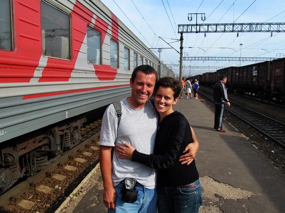 Renato abraçado com Glória, já de cabelo curtinho, em frente ao trem Blog Vem Por Aqui