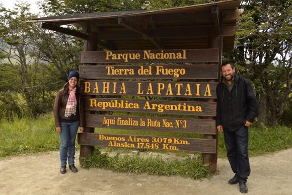 Glória e Renato ladeando a placa de madeira do Parque Nacional Tierra del Fuego que tem a inscrição no final Alasca 17.848 km Blog Vem Por Aqui