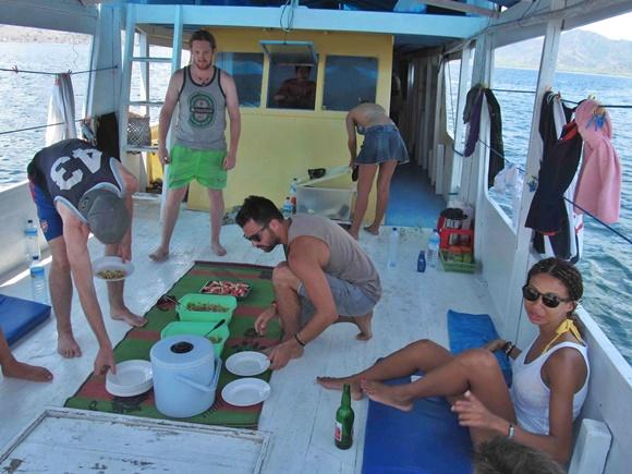 Pessoas pegando o almoço em potes de plástico no meio do barco Blog Vem Por Aqui