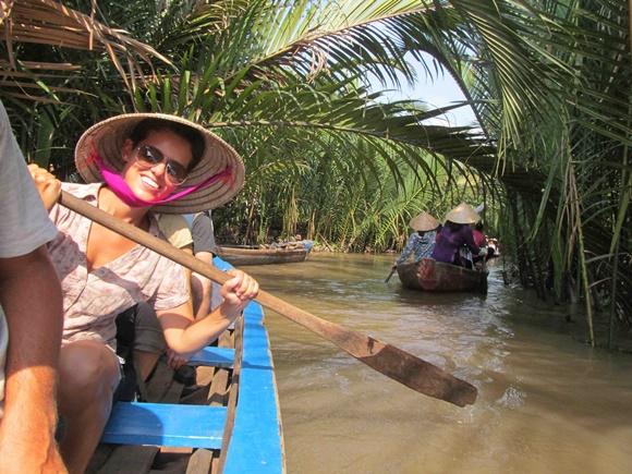 Glória remando numa canoa de chapéu típico vietnamita, em palha e formato de cone, de óculos escuro e sorrindo Blog Vem Por Aqui