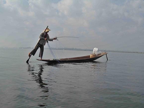 Pescador remando com o remo preso na perna estendendo a rede no barco Blog Vem Por Aqui