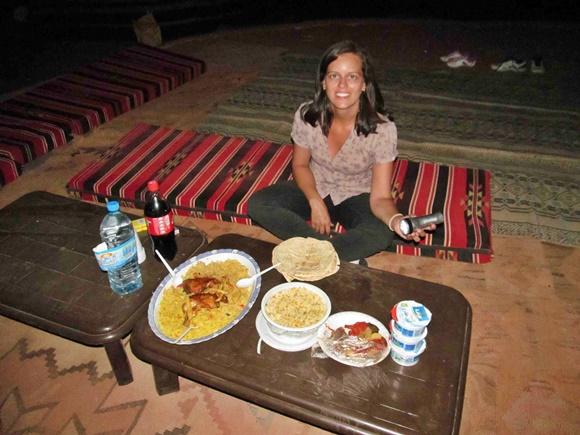 Glória diante da pequena mesa de madeira baixa, com a comida do jantar, sentada numa almofada colorida Blog Vem Por Aqui