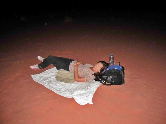 Glória deitada na areia em cima de um lençol com a mochila na cabeça Blog Vem Por Aqui