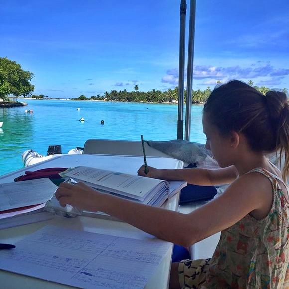 Isabelle estudando diante do mar, dentro do barco Blog Vem Por Aqui