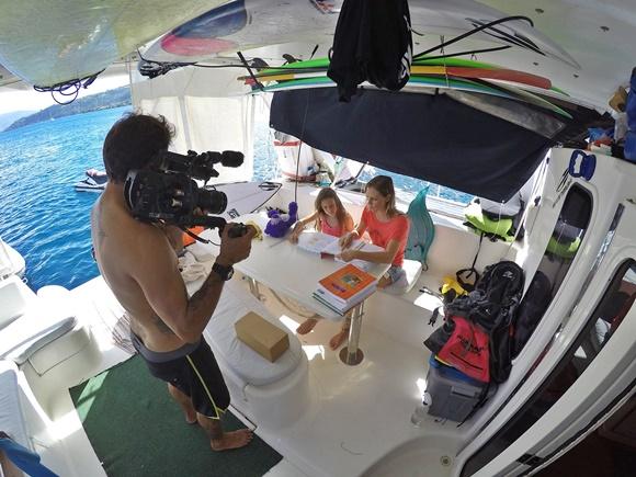 Nalu estudando dentro do barco, sentada numa mesa com a mãe e o pai filmando com uma câmera Blog Vem Por aqui
