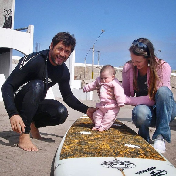 Pato com roupa de neoprene, ajoelhado ao lado da prancha, Nalu ainda bebê na prancha e a mãe, Fabiana, segurando do outro lado Blog Vem Por Aqui