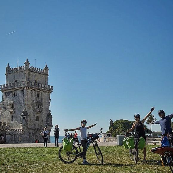 Os três, de bicicleta, em frente à torre de Belém, em Portugal, Blog Vem Por Aqui