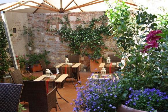 Terraço com mesas com tampo de mármore e cadeiras de vime tipo sofá e muitas plantas na lateral Blog Vem Por Aqui