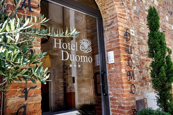 Porta de vidro com o nome do hotel e parede de pedra com o nome em letras de metal Blog Vem Por Aqui