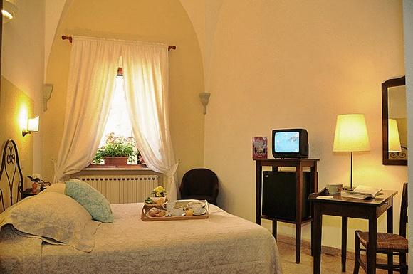 Quarto do hotel com cama feita e bandeja de café em cima, janela na lateral com cortina, mesinha com TV antiga à frente e mesa com cadeira do lado e espelho Blog Vem Por Aqui