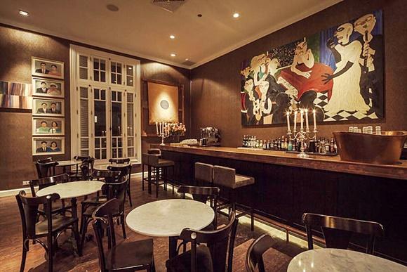 Bar do hotel com quadro enorme atrás do balcão e quadro menores numa parede ao lado da porta, no centro do salão, há várias mesas Blog Vem Por Aqui
