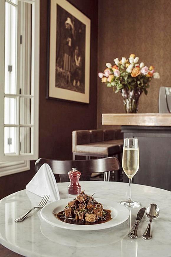 Mesa de mármore no restaurante com um prato com cubos de carne, talheres ao lado, saleiro e taça de espumante à frente Blog Vem Por Aqui