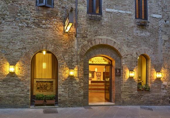 Fachada do hotel em pedra com porta de vidro e janelas compridas de vidro Blog Vem Por Aqui