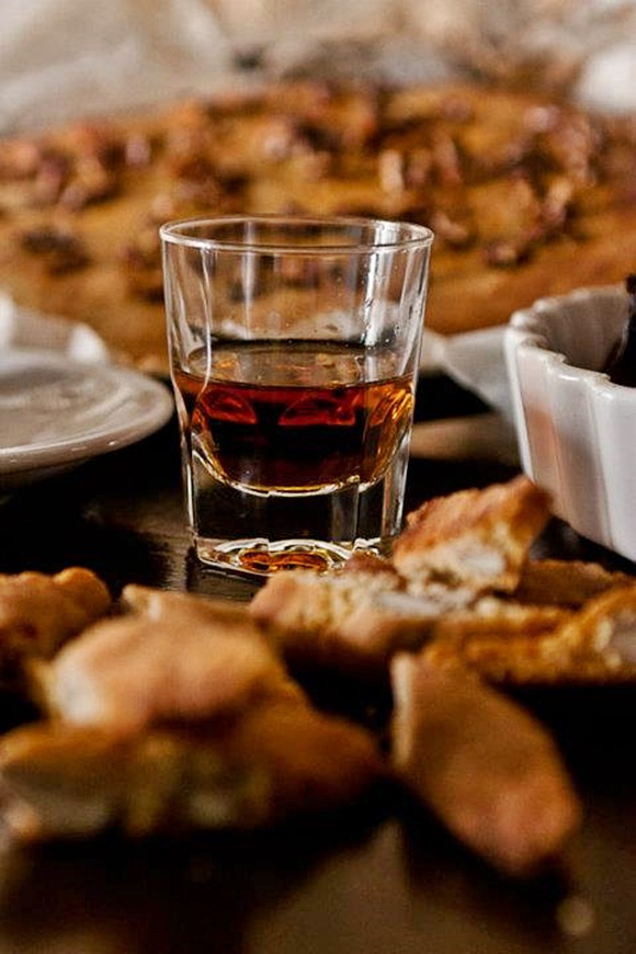 Copo com vin santo e biscoitos em volta, desfocados Blog Vem Por Aqui