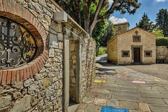 Entrada da vinícola com parede de pedra onde está o portal de entrada e casinha de pedra ao fundo Blog Vem Por Aqui