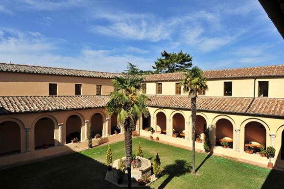Pátio do hostel com prédios em volta e gramado verde com palmeiras no meio Blog Vem Por Aqui