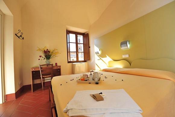 Quarto com cama grande com bandeja com café e toalhas em cima, mesinha com cadeira e janela na lateral Blog Vem Por Aqui