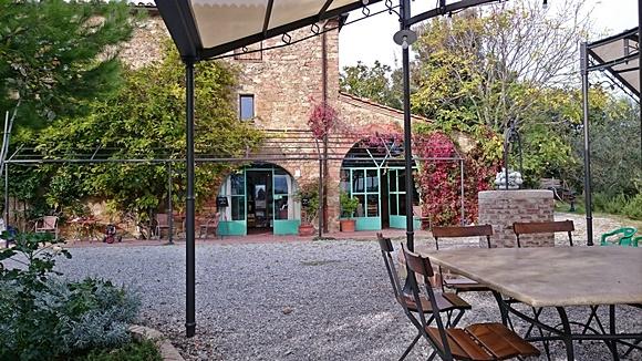 Frente da propriedade com portas verdes vista de uma das mesas do pátio Blog Vem Por Aqui