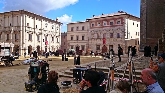 Prédios que rodeiam a praça com bandeiras estilizadas e pessoas observando as filmagens Blog Vem Por Aqui