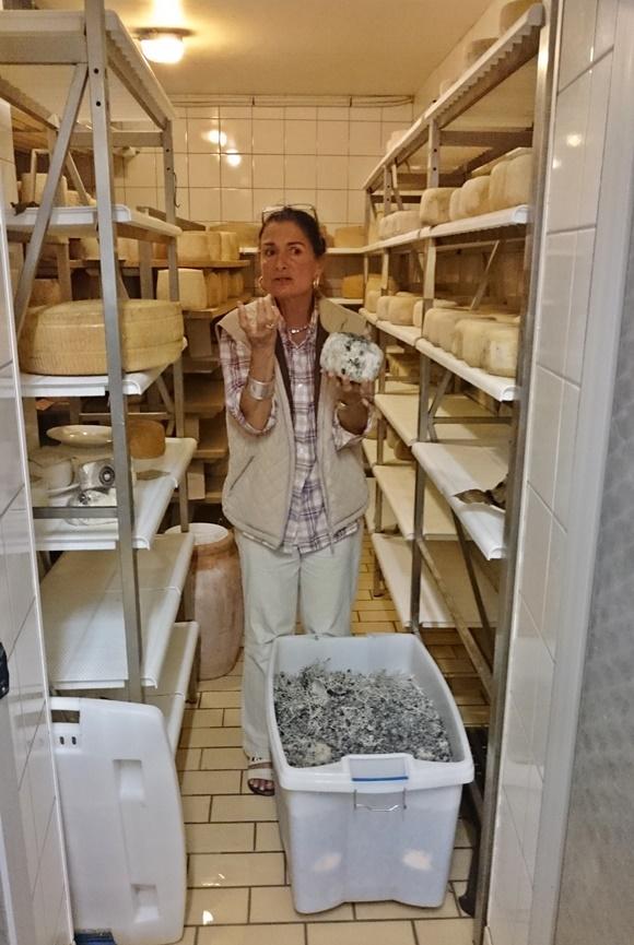 Dona da propriedade com queijo na mão explicando preparação e conserva Blog Vem Por Aqui