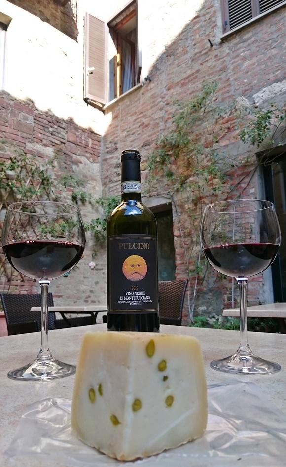 Taças de vinho com pedaço de queijo e garrafa de vinho no meio, em cima da mesa com vista para a parede de pedra Blog Vem Por Aqui