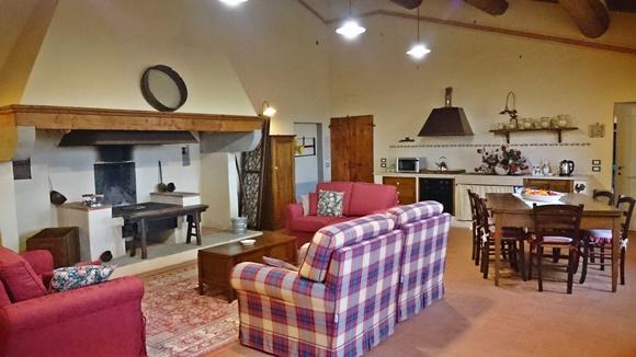 Sala de convivência com sofá xadrez e outros vermelhos diante do fogão a lenha/lareira Blog Vem Por Aqui