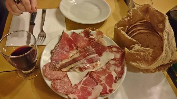 Copo de vinho, prato com frios e cesta de pães Blog Vem Por Aqui