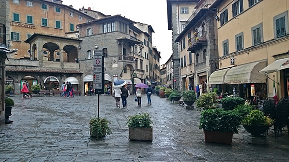 Ruas de pedra com pessoas andando com guarda-chuvas Blog Vem Por Aqui