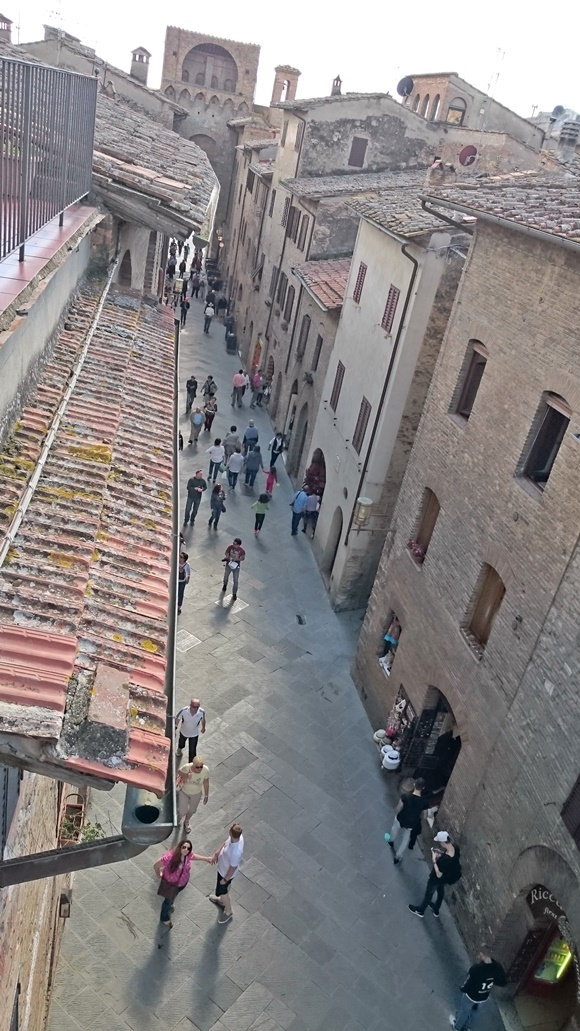 Vista da janela para o centro com pessoas andando nas ruas Blog Vem Por Aqui