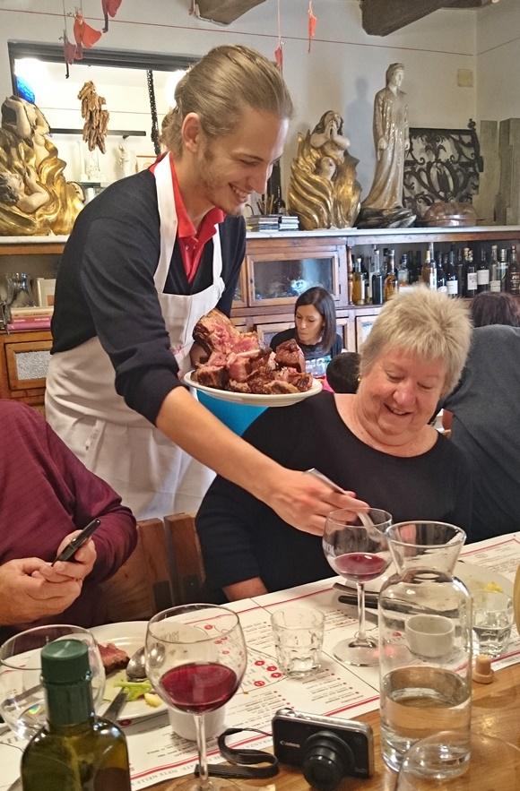 Garçom servindo bisteca para senhora idosa que sorri Blog Vem Por Aqui