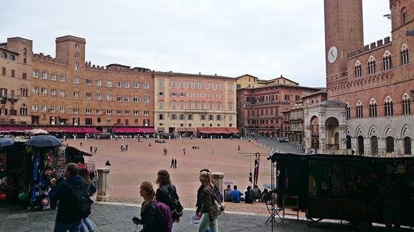 Praça com prédios rodeando e pessoas passando na frente Blog Vem Por Aqui