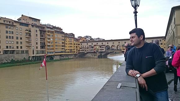 Mateus observando o outro lado do Arno com a ponte de fundo Blog Vem Por Aqui
