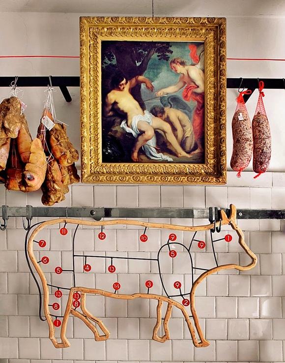 Quadro com pintura antiga, com peças de frios ao lado e, abaixo, figura estilizada de um boi vazado com números indicando cada parte do animal Blog Vem Por Aqui