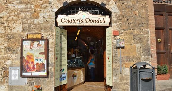 Frente da sorveteria com parede de pedra e placa com nome em cima da porta Blog Vem Por Aqui