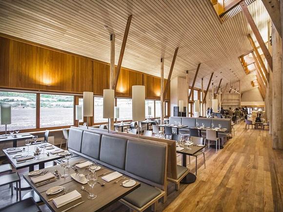 Restaurante do hotel com teto e colunas de madeira e mesas com poltronas conjuntas de quatro lugares Blog Vem Por Aqui