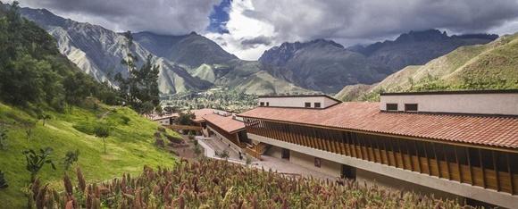 Prédio do hotel visto de cima com montanhas ao fundo, vale na frente e plantação de milho na parte dianteira da foto Blog Vem Por Aqui