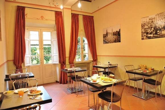 Salão do café com mesinhas com comidas em cima e portas com cortinas vermelhas que dão para o pátio