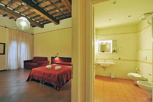 Quarto com cama e sofá ao lado, tento de madeira e no canto direito banheiro grande Blog Vem POr Aqui