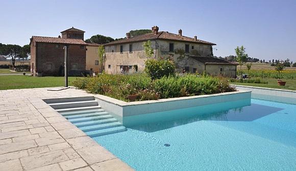 Propriedade com piscina clara e com uma pequena escada entrando para a água, em frente, um jardim Blog Vem Por Aqui
