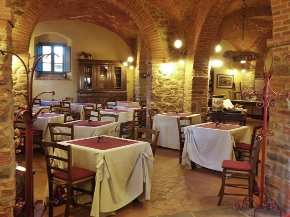 Restaurante com paredes de tijolos de pedra e mesas com cadeiras de madeira, toalhas brancas com detalhe em vinho Blog Vem Por Aqui