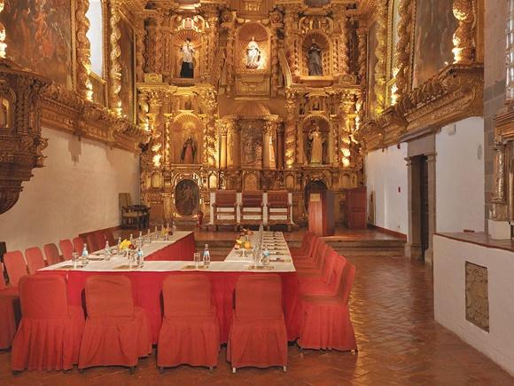 Mesa grande em forma de U com cadeiras com capa vermelha, diante de altar cheio de imagens Blog Vem Por Aqui