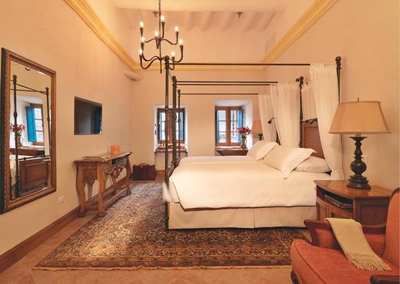 Quarto visto da lateral com espelho grande na parede, ao lado de um aparador e uma TV e em frente a uma cama grande com dossel Blog Vem Por Aqui