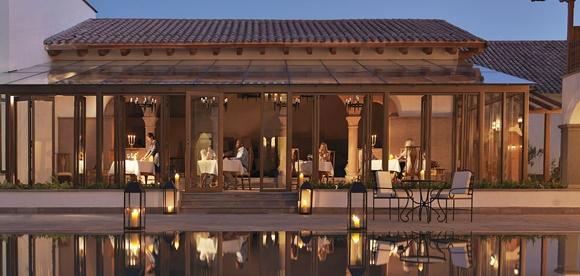 Restaurante do hotel ao anoitecer com lago na frente, parede de vidro e mesas ocupadas por casais e iluminadas por velas Blog Vem Por Aqui